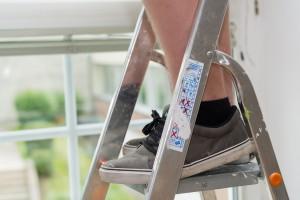 Füsse auf einer Aluleiter sollen Sicherheit und Unfallgefahr zeigen